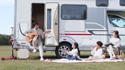 캠핑카 앞에서 가족을 위해 기타를 연주하는 아빠