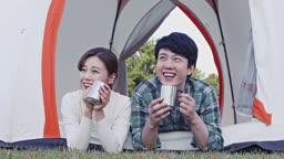 텐트 안에 누워서 함께 커피를 마시며 웃고 있는 부부