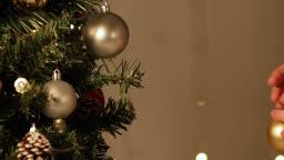 크리스마스 트리에  크리스마스 오너먼트를 장식하는 여자의 손