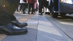 서울 버스정류장에서 출퇴근길 버스를 기다리는 직장인 남성의 발 옆모습