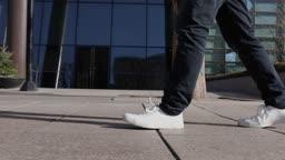 서울 빌딩 앞 인도를 운동화를 신고 걷는 성인 남성의 다리 옆모습