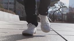 서울 빌딩 앞 인도를 운동화를 신고 걷는 성인 남성의 발 앞모습