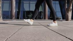 서울 빌딩 앞 인도를 운동화를 신고 걷는 성인 여성의 다리 옆모습