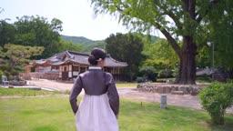 고택 마당을 거니는 전통 한복 입은 여자