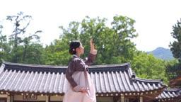 고택 앞 손으로 햇빛 가리는 전통 한복 입은 여자