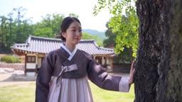 고택 앞 나무를 만지며 걷는 전통 한복 입은 여자