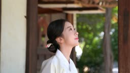 대청마루에 앉아 환하게 웃는 전통 한복 입은 여자