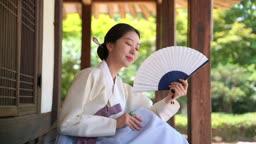 대청마루에 앉아 부채질하는 전통 한복 입은 여자