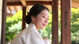 대청마루에 앉아 하늘을 바라보는 전통 한복 입은 여자