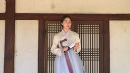 부채를 펴 부채질하는 전통 한복 입은 여자