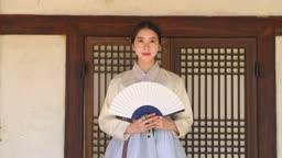 부채를 들고 환하게 웃는 전통 한복 입은 여자