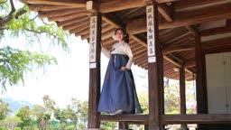 대청마루에 서 하늘을 바라보는 전통 한복 입은 여자