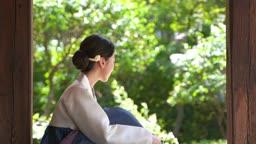 대청마루에 앉아있는 전통 한복 입은 여자