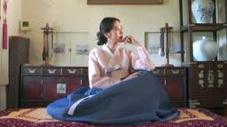 방 안에 앉아 환하게 웃는 전통 한복 입은 여자