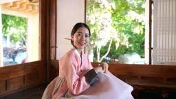 고택 안에 앉아 환하게 웃는 전통 한복 입은 여자