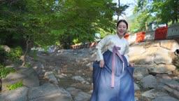 숲을 거니는 전통 한복 입은 여자
