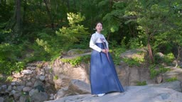 바위 위에 서 있는 전통 한복 입은 여자