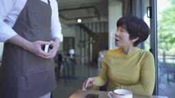 카페에서 스마트 결제하는 중년 여성