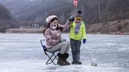 강원도 홍천군 겨울 저수지에서 얼음 빙어 낚시를 즐기는 엄마와 아들