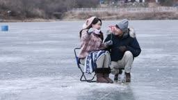 강원도 홍천군 겨울 저수지에서 얼음 빙어 낚시를 즐기는 연인