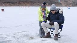 강원도 홍천군 겨울 저수지에서 얼음 빙어 낚시를 즐기는 아빠와 아들