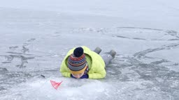 강원도 홍천군 겨울 저수지에서 얼음 안을 보고 있는 남자 어린이