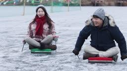 강원도 홍천군 겨울 얼음 저수지 위에서 썰매타는 연인