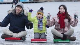 강원도 홍천군 겨울 얼음 저수지 위에서 썰매타는 가족