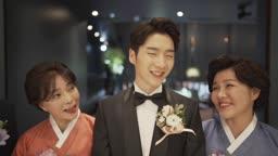 결혼식장에서 환하게 웃는 신랑과 양가 부모님