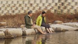 오랜 친구와 강물에 발 담그며 장난치는 60대 남자