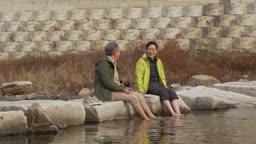 오랜 친구와 강물에 발 담그고 같이 웃는 60대 남자