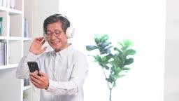 스마트폰에 연결된 헤드폰으로 음악을 들으며 즐거워하는 60대 남자