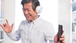 스마트폰에 연결된 헤드폰으로 음악을 들으며 춤추는 60대 남자