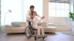 휠체어에 앉은 60대 여자의 운동을 돕는 60대 남자