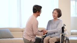 휠체어에 앉은 60대 여자를 격려 중인 60대 남자