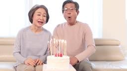생일 케이크의 초를 함께 불며 끄는 60대 부부
