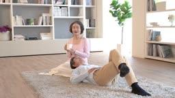 거실에서 함께 쉬며 대화를 나누는 60대 부부