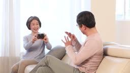 거실에서 카메라로 사진 찍어 주며 즐거워하는 60대 부부