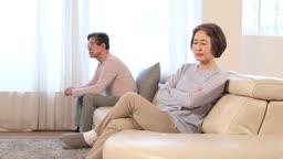 부부 싸움 후 거실 소파에 앉아 대립 중인 60대 노인 부부