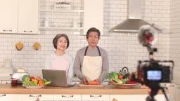 요리하며 주방에서 영상을 촬영하는 요리 크리에이터 60대 부부