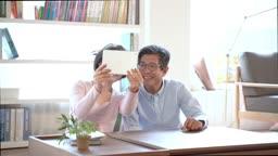태블릿기기로 화상 통화를 하는 60대 부부