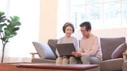 거실 소파에 앉아 대화 나누며 노트북하는 60대 부부