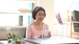 커피 마시며 디지털기기를 이용하는 60대 여자