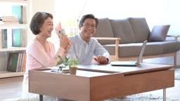 스마트폰으로 통화하며 행복해하는 60대 부부