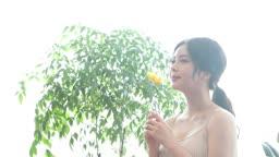 꽃 한 송이를 들고 미소를 짓는 20대 여성