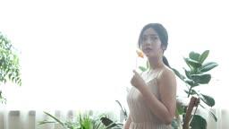 꽃 한 송이를 들고 있는 20대 여성