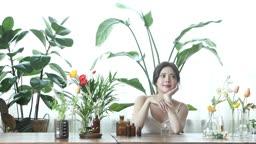 실내 정원에서 천연 화장품 용기를 만지는 20대 여성