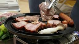 집콕문화 집에서 캠핑 분위기 내며 고기 자르는 모습