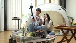 집콕문화 집에서 캠핑 분위기 내며 셀프카메라 촬영하는 커플 모습