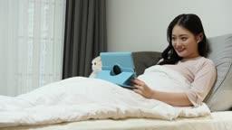 집콕문화 집 침실에서 고양이와 함께 스마트패드 보면서 호캉스 즐기는 젊은여자 모습